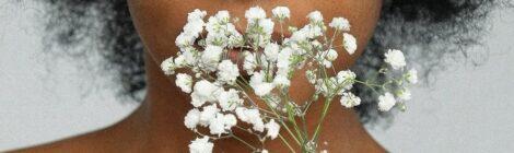 primo piano di ragazza che annusa un fiore bianco