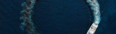 una nave naviga tra le onde del mare blu formando, con la sua scia, un cerchio sull'acqua